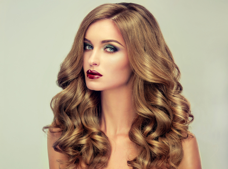 Mooi meisje met lang golvend haar. fair-haired model met krullend kapsel en trendy make-up. Bright paarse lips