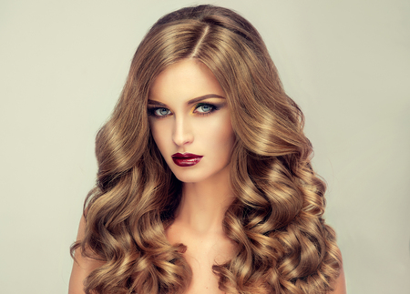 color model: Beautiful girl with long wavy hair .  fair-haired  model  with curly hairstyle   and fashionable makeup . Bright purple lips