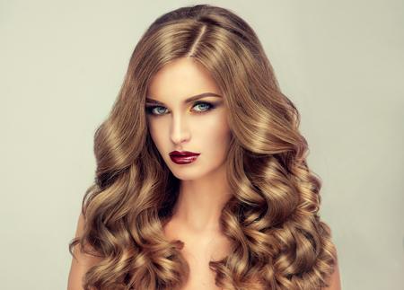 Mooi meisje met lang golvend haar. blond model met krullend kapsel en modieuze make-up. Helder paarse lippen