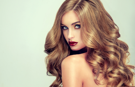 Hermosa chica con el pelo largo y ondulado. Modelo rubio con el peinado rizado y maquillaje de moda. labios morados brillantes Foto de archivo