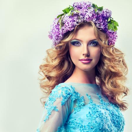 Mooi model in een krans van lila bloemen op het hoofd, met krullend lang haar. Afbeelding van de jeugd en de zomer frisheid.