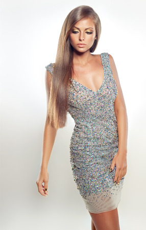 evening gown: Portrait of fashion model dressed in a silver evening gown, demonstrating straight, dense, shiny hair. Stock Photo