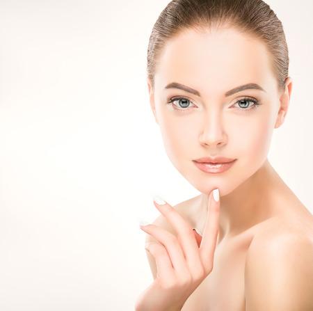 Yong, superbe modèle toucher son visage et démontrer la fraîcheur et womans visage propre peau. Soins de la peau et cosmétologie.