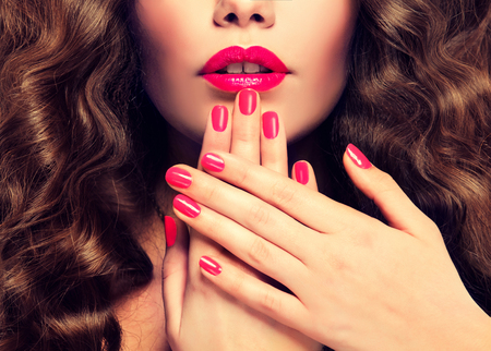 fuchsia color: Beautiful girl showing crimson manicure, lipstick and dense, curly hair.