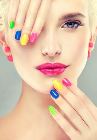 Stijlvolle blonde meisje met lichte make-up en kleurrijke nagellak op je nagels. Lente en zomer uitstraling en oorbellen kralen