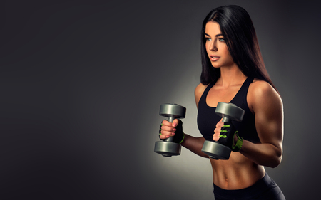 body shape: Beautiful fitness woman lifting dumbbells . Fitness sporty woman showing her well trained body . Stock Photo