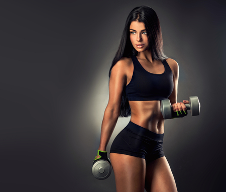 Beautiful fitness woman lifting dumbbells . Fitness sporty woman showing her well trained body. 版權商用圖片 - 62540841