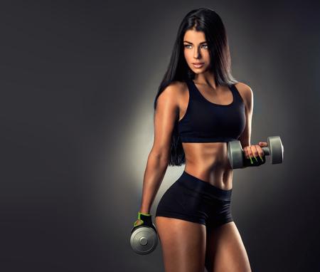 Schöne Fitness Frau Hanteln heben. Fitness sportliche Frau ihr gut ausgebildeten Körper zeigt. Standard-Bild
