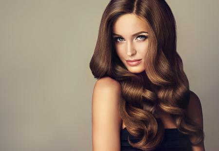 Brunette fille avec de longs et brillants cheveux ondulés. Beau modèle avec coiffure bouclée. Banque d'images - 62540848