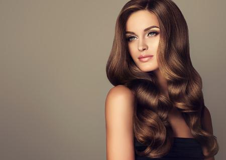 Brunette dziewczyna z długimi włosami i błyszczące faliste. Piękny model z kręcone fryzura.
