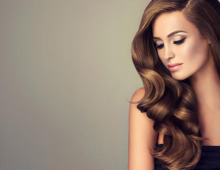 Brunette dziewczyna z długimi włosami i błyszczące faliste. Piękny model z kręcone fryzura. Zdjęcie Seryjne