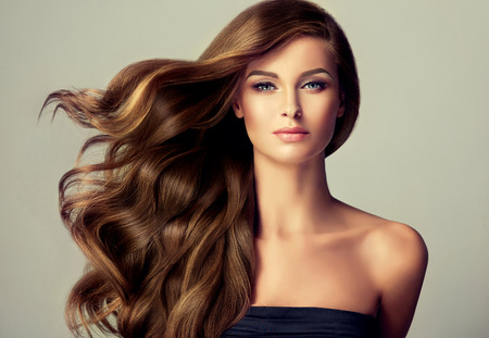 brown hair: Brunette  girl with long  and   shiny wavy hair .  Beautiful  model with curly hairstyle .