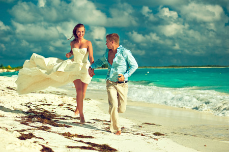 Wedding on the beach . Young beautiful couple get married on the beach on a tropical island .