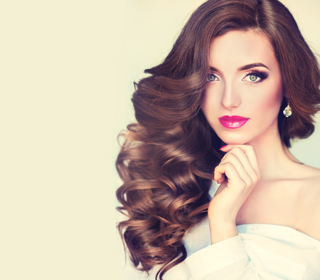 beautiful model: Beautiful model brunette with long curled hair and jewelry earrings.