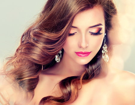 Beautiful model brunette with long curled hair and jewelry earrings.