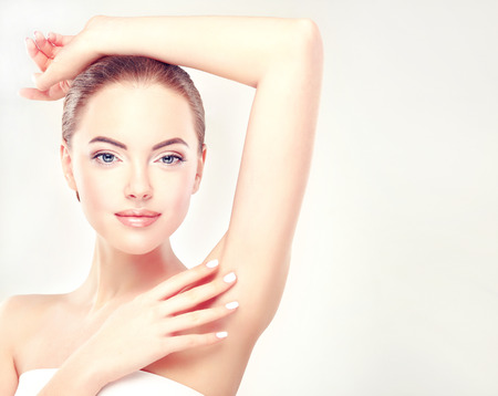 depilacion: Mujer joven que levanta sus brazos y mostrando las axilas limpias, la depilación suave piel clara .Beauty retrato.
