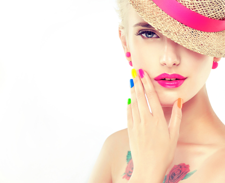 Stylish blonde girl in a straw hat with bright makeup and colorful nail Polish on her nails .