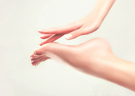 Beautiful womens hand touches her well-groomed feet. Spa ,scrub and foot care . Stock Photo