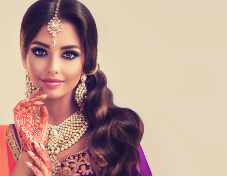 Portret van mooi Indisch meisje. Mehndi schildert op haar handen en kundan sieraden. Traditionele Indiase kostuum.