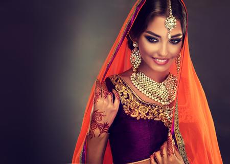 Young hindu woman model with tatoo mehndi and kundan jewelry . Traditional Indian costume lehenga choli . Banque d'images