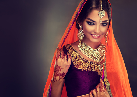 Modelo da mulher hindu nova com mehndi tatoo e jóias kundan. choli traje lehenga indianos tradicionais.