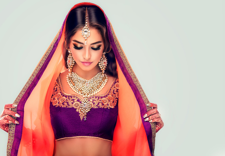 Young hindu woman model with tatoo mehndi and kundan jewelry . Traditional Indian costume lehenga choli . Banco de Imagens