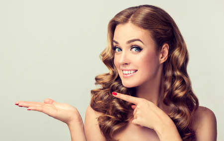 Surprised woman demonstrates invisible product .Beautiful girl with curly hair pointing to the side. Bright facial expression. Standard-Bild