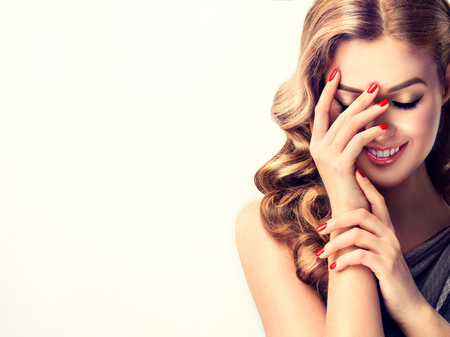 Beautiful woman with curly hair and red nails manicure . Girl laughs shyly closes her face with a hand . Stock Photo