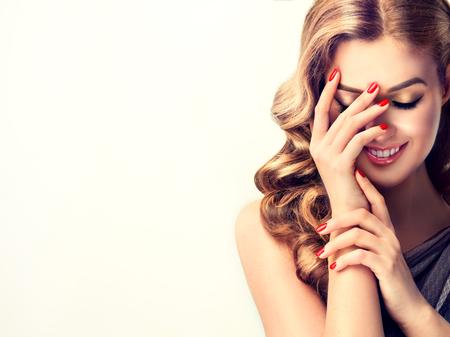Belle femme avec des cheveux et des ongles rouges bouclés manucure. Fille rit ferme timidement son visage avec une main.
