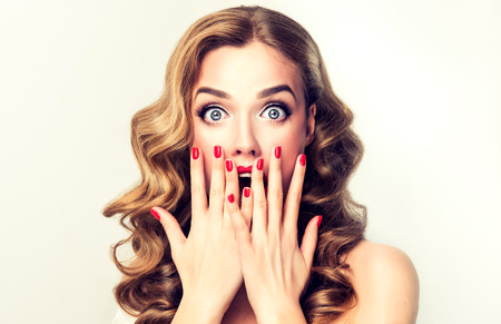 Facial expression of young woman displaying  shock, astonishment  and amazement. Beautiful girl with curly hair, perfect mack up and manicure.