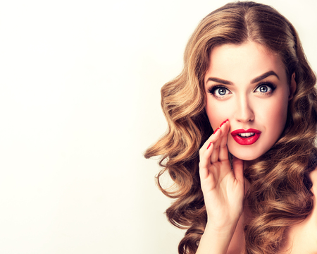Beautiful girl with bright makeup and curly hair telling a secret. Expressive facial expressions.