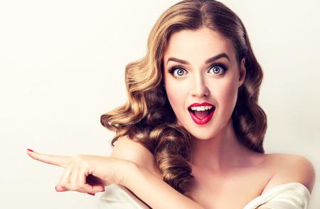 Une femme surprise montre un produit invisible. Belle fille aux cheveux bouclés pointant sur le côté. Expression du visage lumineux.