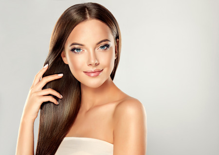 Krásný model dívka s lesklými hnědé rovné dlouhé vlasy. Péče a vlasové přípravky