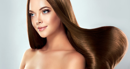 Beautiful model girl with shiny brown straight long hair . Care and hair products Stock Photo
