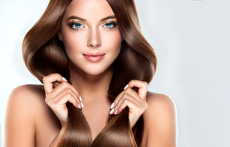 champu: modelo muchacha hermosa con el pelo largo recto marrón brillante. Cuidado y productos para el cabello. Foto de archivo