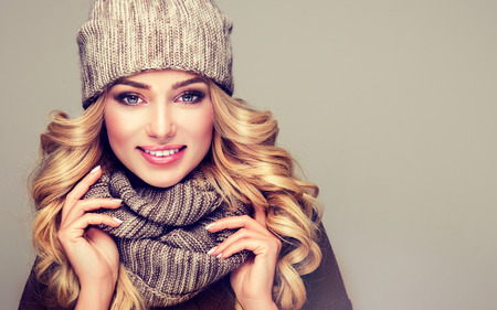 Trendy warm winter clothes. Nice, young,smiling blonde woman dressed in gray wool winter hat and scarf. Stock Photo