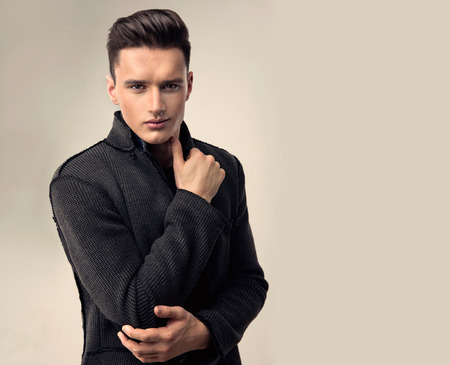 Portrait of a handsome young man with trendy hairstyle, dressed in a stylish and fashionable wool jacket.