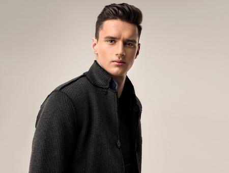 Porträt einer schönen jungen Mann mit modischer Frisur, in einem stilvollen und eleganten Wolljacke gekleidet. Standard-Bild