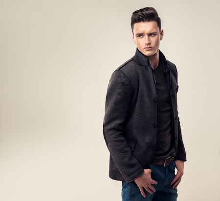 Porträt einer schönen jungen Mann mit modischer Frisur, in einem stilvollen und eleganten Wolljacke gekleidet.
