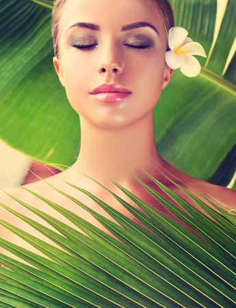 Close-up portrait of gorgeous model between tropical leafs. Beauty and Spa treatment concept. Stock Photo