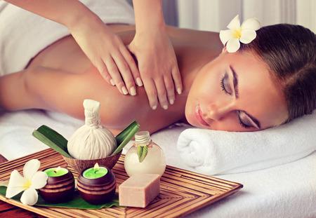 Jonge dame die op een massagetafel ligt en een massagebehandeling krijgt. Spa- en lichaamsmassage.
