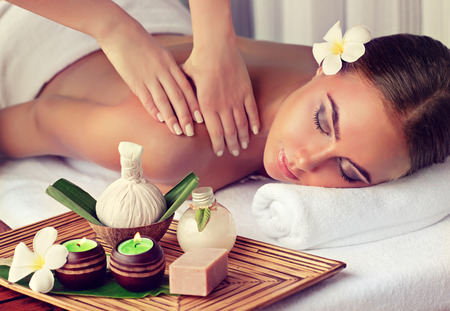 Young lady who lays on massage table and gets massage treatment.Spa and  body massage. Stock Photo