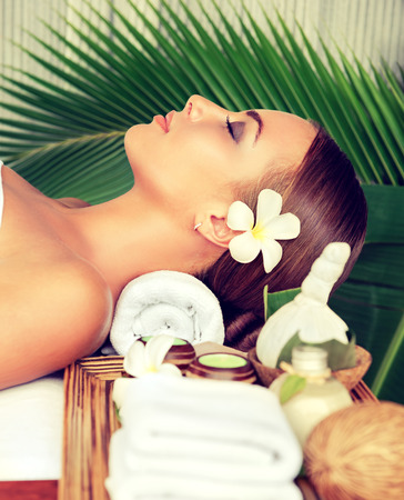 welling: Portrait of young girl who lays on massage table, surrounded comfortable atmosphere of spa-salon. Beauty and Spa treatment concept.