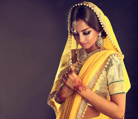 Beautiful indian girl . Young hindu woman model  with tatoo mehndi  and kundan jewelry . Traditional Indian costume, yellow saree.