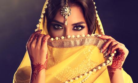 아름다운 인도 소녀. 문신 멘디와 kundan 보석 젊은 힌두교 여자 모델입니다. 전통적인 인도 의상, 노란색 사리. 스톡 콘텐츠
