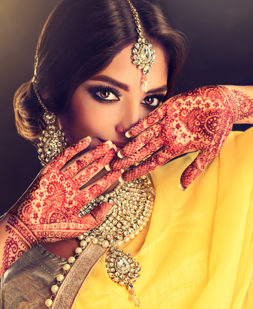 Beautiful indian girl . Young hindu woman model  with tatoo mehndi  and kundan jewelry . Traditional Indian costume, yellow saree.