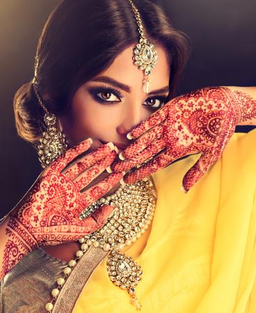 Mooi Indisch meisje. Jonge hindoe vrouw model met tatoo mehndi en kundan sieraden. Traditionele Indiase kostuum, gele saree.
