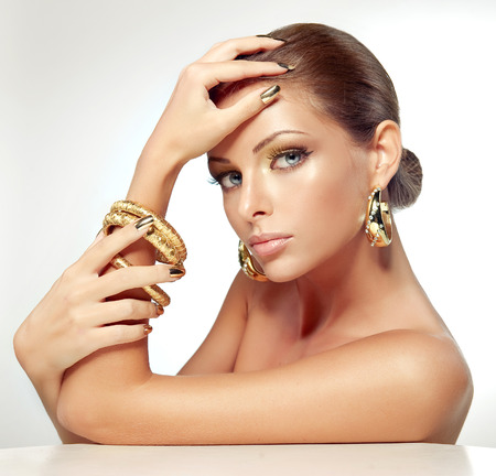 Portrait of young model in golden make up, bright gilded accessories-bracelets and earrings, with gold manicure on fingers.