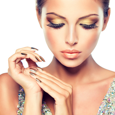 Golden make up, bright gilded manicure and elegant gesture. Close up portrait of  attractive woman model.
