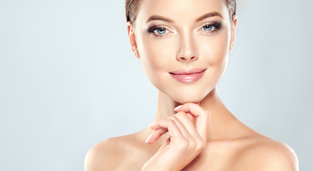 woman beauty: Beautiful Young Woman with Clean Fresh Skin touch own face . Facial treatment . Cosmetology , beauty and spa . Stock Photo